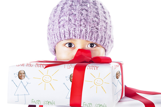 Boy hiding behind Christmas gifts isolated in white